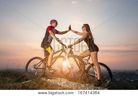 Cyclist Couple With Mountain Bikes On The Hill At Sunset