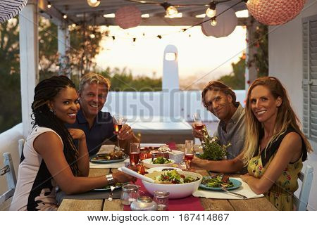 Two couples having dinner on a roof terrace look to camera