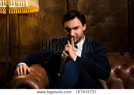 Rich businessman sitting on sofa and asking for silence. Luxury man with much money having secret concerning mafia. Wealth concept.