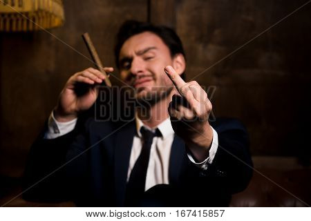 Global conspiracy, disrespect, swindler. Handsome man sitting with cigar on sofa in restaurant. Rich man challenging whole of society, cheater, disrespect.