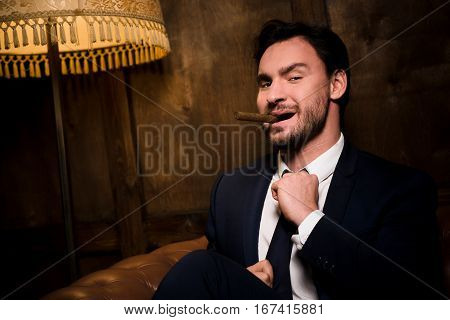 Ambitious careerist smoking expensive cigar while spending free time in restaurant. Handsome bearded man looking at camera.