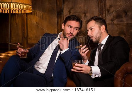 Luxury men sitting on sofa and smoking cigars in men's club and solving global problems. Collusion in business and global conspiracy between two successful businessmen.