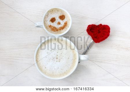jolly man of the cups a frothy cappuccino and heart symbol top view / good mood with a drink