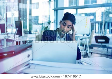 Stressed businesswoman sitting at desk in office