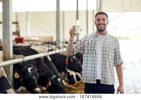 agriculture industry, farming, people and animal husbandry concept - happy young man or farmer with bottle of cows milk in cowshed on dairy farm