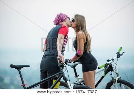 Romantic Young Couple Kissing On Bicycles