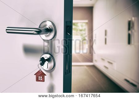 Digitally generated image of open door with house key against walk in wardrobe in bedroom