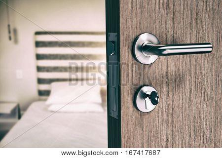 Brown door with doorknob and key against bedroom