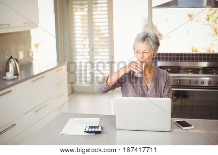Senior woman drinking water while sitting at table with laptop in kitchen