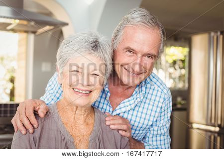 Portrait of cheerful senior man embracing wife at home