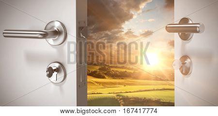 Closeup of wooden door with metallic doorknob against country scene