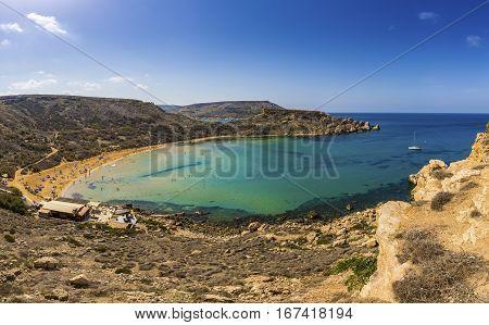 Ghajn Tuffieha Malta - Beautiful summer day at Ghajn Tuffieha sandy beach with sail boat blue sky and crystal clear green sea water