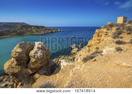 Malta - Huge rocks and Ghajn Tuffieha tower on a hot summer day with crystal clear blue sea water and sail boat