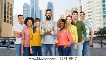 travel, tourism, diversity, ethnicity and people concept - international group of happy smiling men and women over dubai city street background