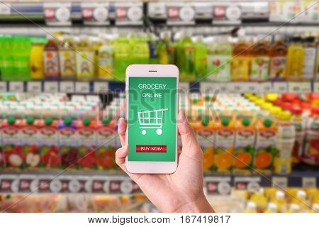 woman hand holding mobile with grocery online on screen with blur supermarket background