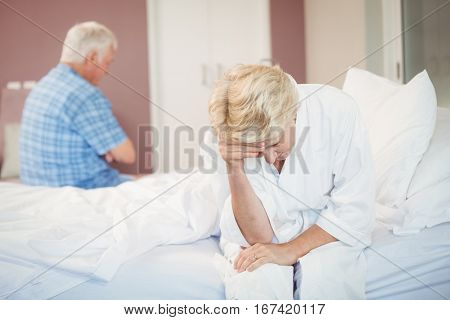 Tensed senior couple sitting in bedroom at home