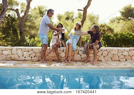 Two couples socialising by a pool outdoors make a toast
