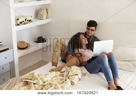 Teenage couple relaxing in bedroom look at each other