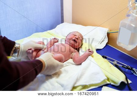Newborn child seconds and minutes after birth. Doctor hands with new born baby. Medical check up of health and reflexes of child. New life, beginning, healthcare.