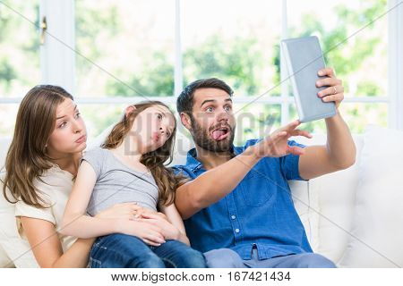 Family making face while clicking selfie with digital table at home