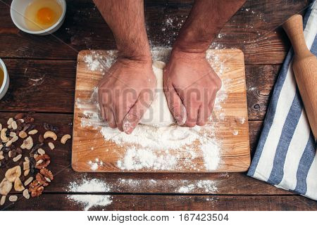 Man kneading dough on cutting board flat lay. Top view on kitchen workplace with baker hands working with raw pastry. Homemade bakery, cooking process concept