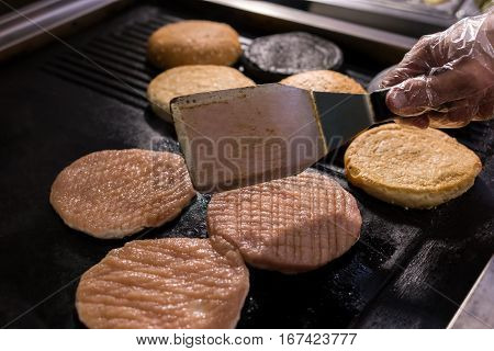 Raw burger meat on pan. Hand holding kitchen spatula. Top quality ingredients for hamburgers.