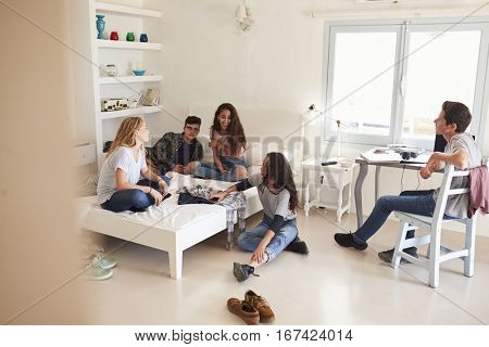 View from doorway of teenage friends hanging out in bedroom