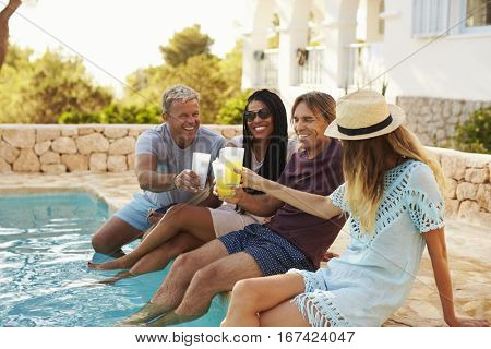Two couples make a toast with legs dipping in swimming pool