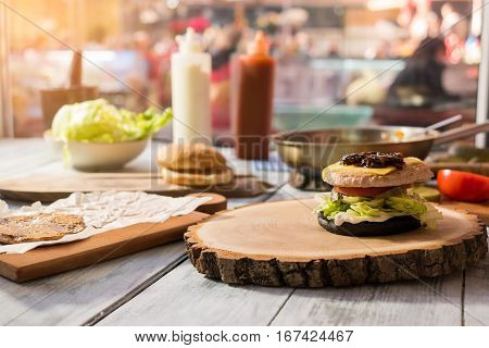 Burger ingredients on wood board. Meat, vegetables and bun. Layer by layer.