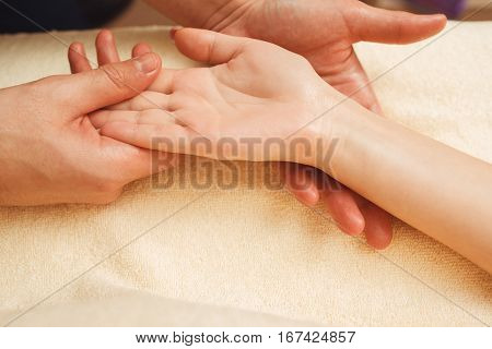 Palmist reading future through study of palm closeup. Man chiromancer holding female hand and attentively studying it, free space. Foretelling, mystery, fortune, magic concept