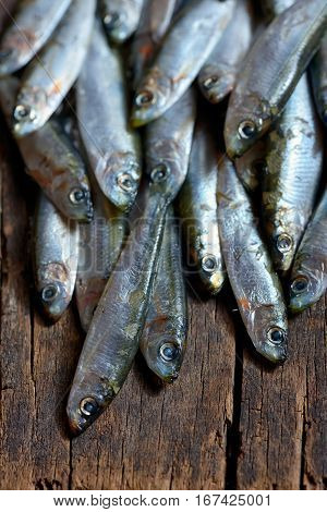 Anchovies (hamsi) on old table wood, close up