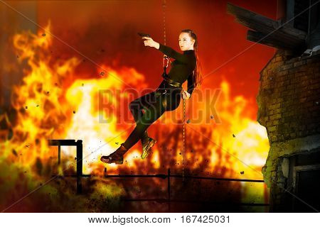 Girl with a gun hanging on the climbing equipment a fire in the background
