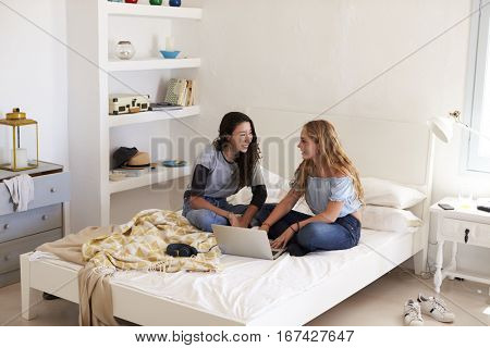 Two girls sitting on bed using laptop looking at each other