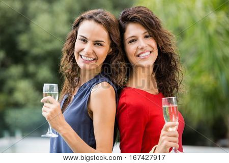 Portrait of smiling female friends holding champagne flutes at resort