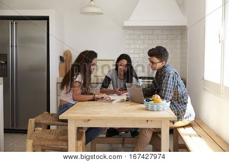 Three teens studying in a kitchen using computers, side view