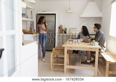 Teenage friends hanging out and studying together in kitchen