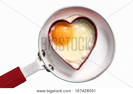 Fry pan with egg in heart shape on white background