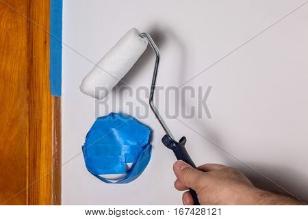 Painters hand with roller and masking blue tape on thermostat and door frame