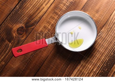 Fry pan with oil on wooden background