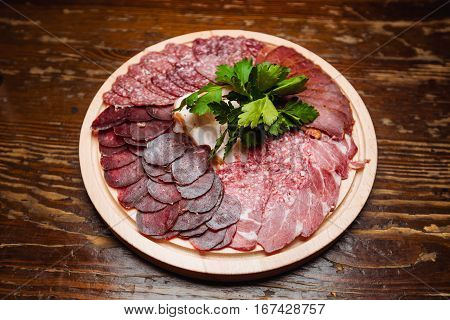 plate with snack cold meats - bacon salami ham parsley on a wooden table