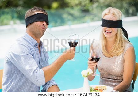 Blindfolded couple holding red wine while sitting at poolside