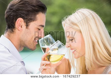 Close-up of couple drinking wine at poolside