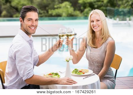 Portrait of happy couple toasting white wine glasses while sitting at poolside