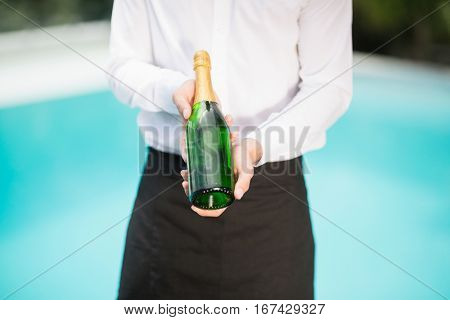 Midsection of waiter holding champagne bottle at poolside
