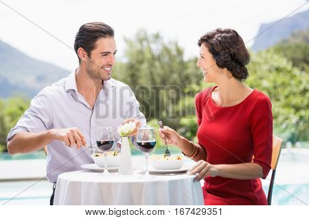 Happy couple having food while sitting at poolside