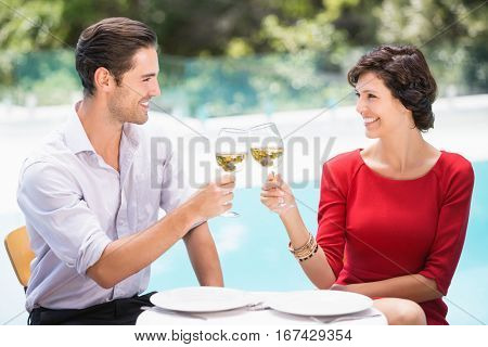 Smiling couple toasting white wine while sitting at poolside
