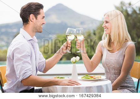 Couple toasting white wine while sitting at poolside