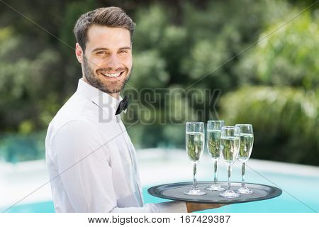 Portrait of happy waiter carrying champagne flutes on tray at poolside
