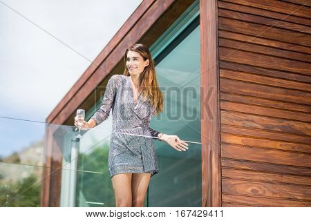 Low angle view of beautiful young woman standing by glass railing at balcony