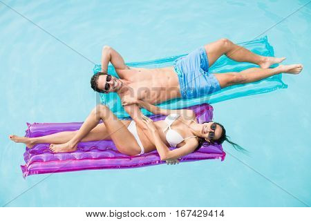 High angle view of cheerful couple relaxing on inflatable raft at swimming pool